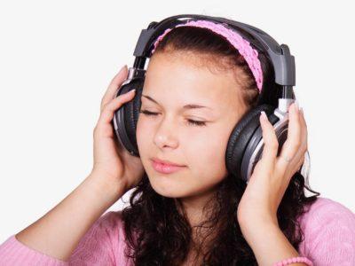 ヘッドフォンで何かを聞く女性
